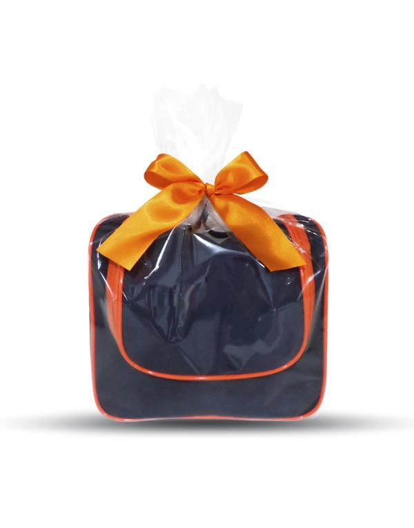Térmica JL possui a modelagem formato baú produzida em poliester 600 azul marinho e vivo como detalhe na cor laranja amntém os alimentos na temperatura imagem da peça embalada para presente com celofane e laço de cetim na cor laranja